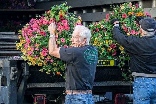men unloading flower baskets from truck