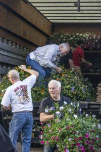 people unloading flower baskets from truck