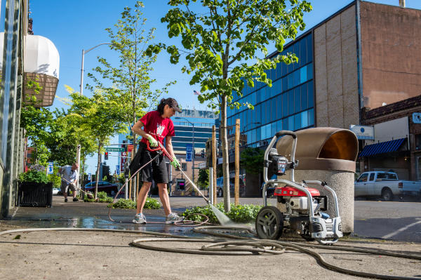 woman power washing sidewalk